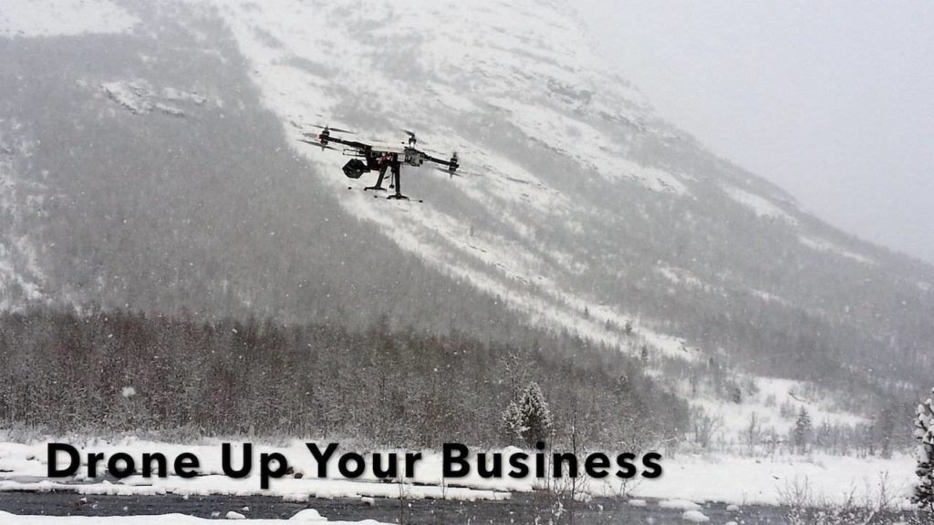 Photo of drone flying in the mountains indicating the use of commercial drones (aka UAVs, UAS, or quadcopters)